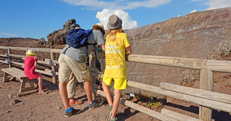 Napoli, Italy - September 6th, 2013: People looking into Vesuvius crater. Two adult and a young boy standing back at the wooden rail surrounding the crater. A girl sitting on a wooden bench on the left. Horizontal image in a sunny day