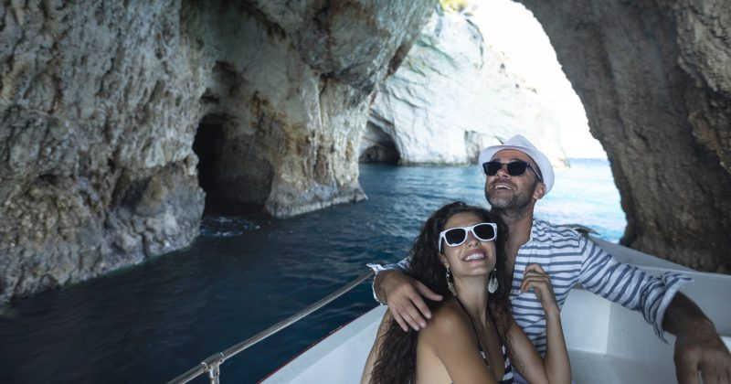 Couple yachting in cave, looking up.